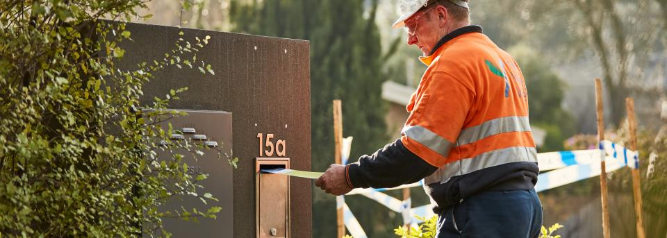 maintenance worker putting mail into letterbox