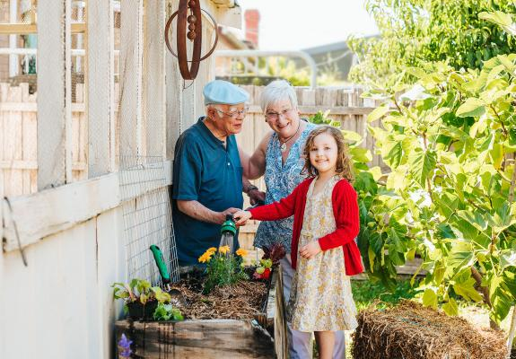 Grandparents and granddaughter watering garden